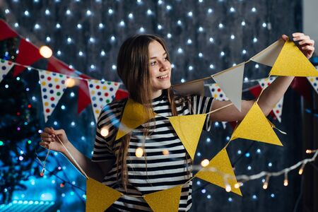 Woman at home hanging christmas lights party flags decorate items for celebration new year