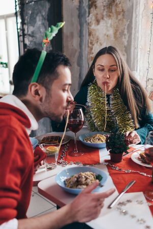 Cheerful friends at the table eating pasta, spaghetti hanging out their mouths. Zdjęcie Seryjne