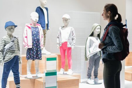 Woman stands outside the childrens store and looks at the clothes on the mannequins.