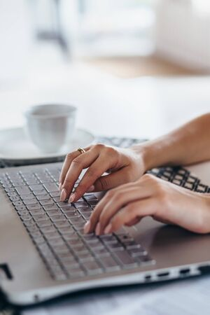 Woman using laptop typing on the keyboard Female hands close up