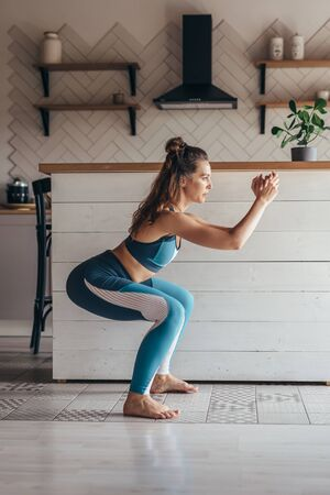 Young woman practicing squats. Woman exercising at home