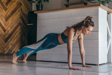 Fit woman working out doing push ups at home. Imagens