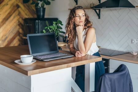 Pensive woman in the kitchen at the table with a laptop