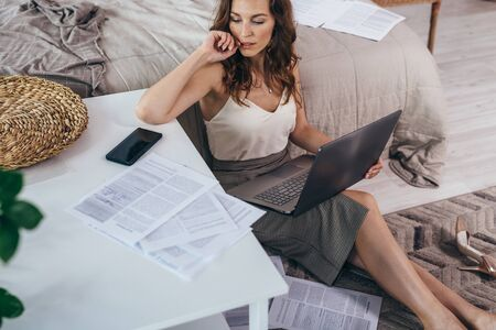 Young woman is sitting on the floor with notebook among documents Imagens