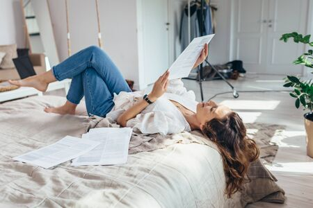 A young woman is lying on a bed in the bedroom reading Imagens