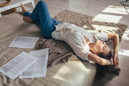 A young woman at home is lying among the papers on the bed and resting Imagens