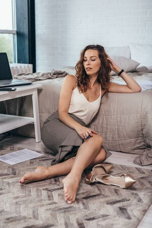 Portrait of a business woman sitting on the floor at home Imagens