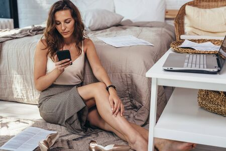 Woman at home sits on the floor with smartphone