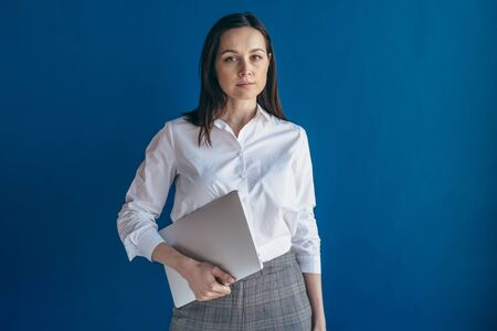Portrait of young serious business woman with laptop looking at camera. Imagens