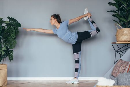 Fit woman exercising at home. Stretching and balancing on one leg.