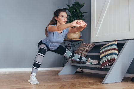 Fit woman stretching legs Lateral Lunge exercise. Imagens