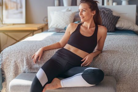Portrait of young female athlete at home. Woman sitting relaxed before workout in bedroom