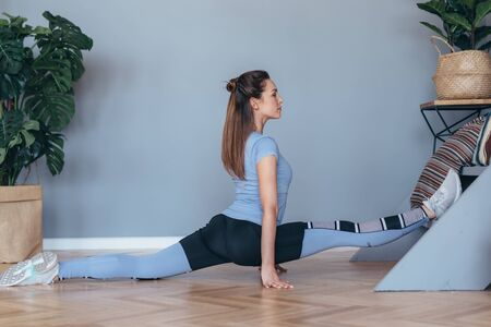 Young fit woman doing the splits working out at home.