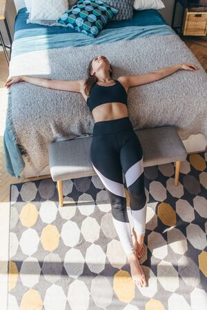 Fitness woman athlete lying on the bed and resting.
