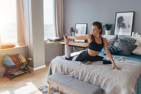 Fit woman doing exercise on bed at home