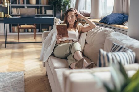 Woman lying on sofa and reading book at home