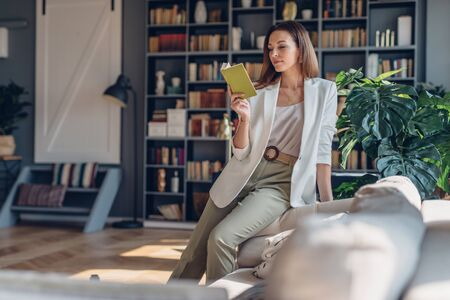 Woman sitting on couch in the morning, reading book at home Imagens