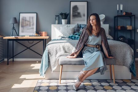 Elegant young woman sitting in bedroom. Home interior