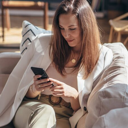 Woman lying on the sofa and using smartphone at home.