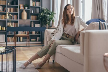 Woman in business attire after work at home resting on couch.