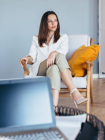 Woman in business clothes sitting on chair.