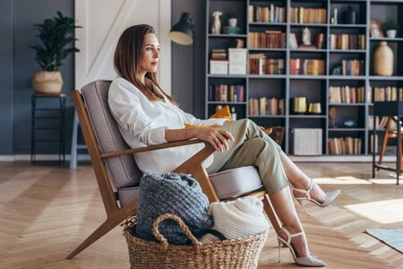 Business woman sitting in a chair at home Imagens