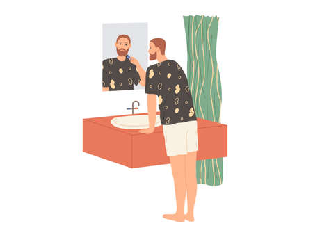 Man shaves his beard with an electric razor while standing in the bathtub by the mirror