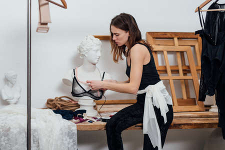 Woman fashion designer tries on a bra on a mannequin Stock fotó