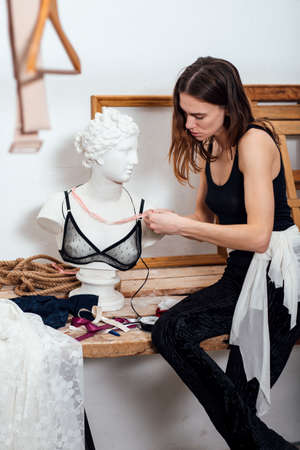Female fashion designer tries on a brassiere on statue