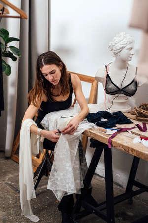 Female lingerie designer works in her workshop. Stock fotó