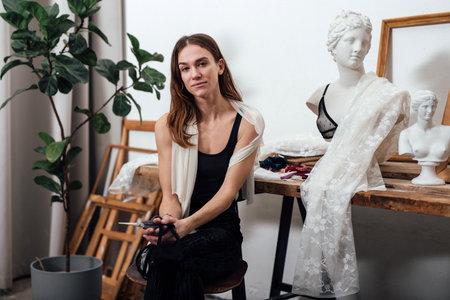 Portrait of a woman lingerie designer sitting in her studio