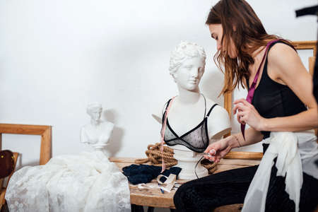 Female fashion designer works in a workshop on womens lingerie
