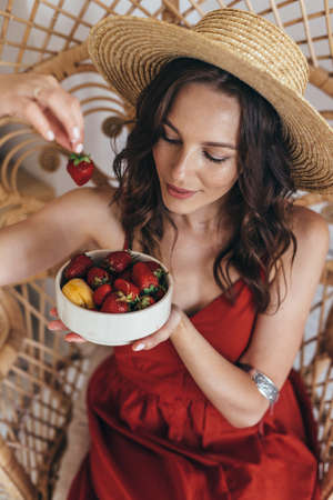 Young woman in a straw hat eating strawberries. Standard-Bild