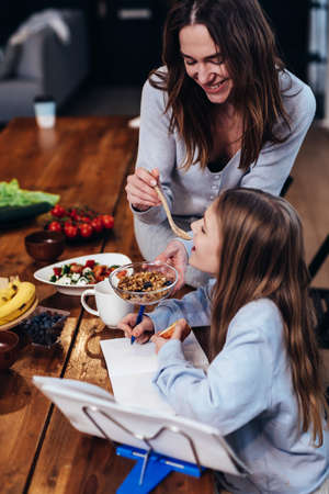 Girl is doing her homework at the kitchen table, and her mother gives her a taste of food with a spoon