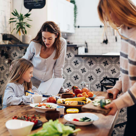Preparing for family dinner, women are setting the table, while the girl is learning her lessons.