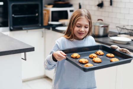 Girl is carrying a tray with cookies that she baked herself.