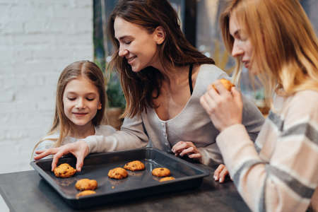 Young woman and her friend are curious about the cookies her daughter made Standard-Bild