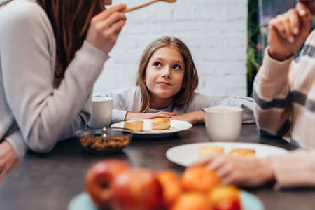 Girl listens to adults talking together at the kitchen table. Standard-Bild