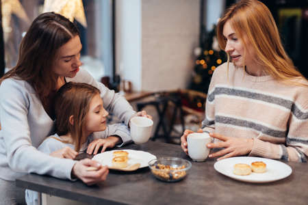 Female friends and a little girl sitting together at the kitchen table Standard-Bild
