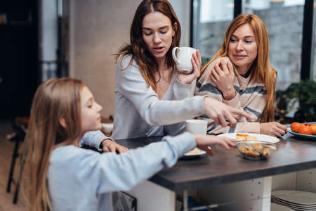 Female friends and a little girl sitting together at the kitchen table, drinking tea and talking Standard-Bild