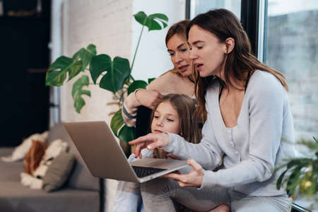 Female friends and a little girl sitting at home on a windowsill watching a movie on a laptop.