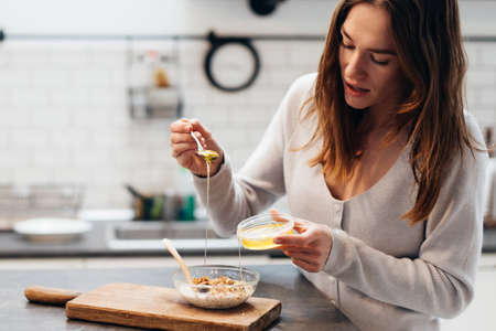 Young woman in the kitchen adds honey to granola