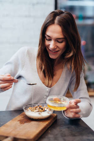 Young woman in the kitchen adds honey to muesli.