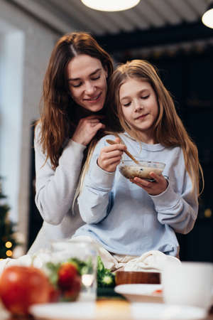 Caring, hugging mother next to her daughter eating granola