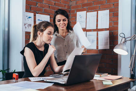 Two female colleagues in office working together.