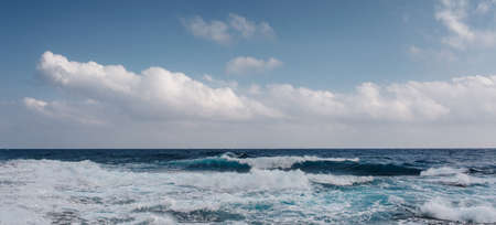 Sea waves crash on the rough rocky shore