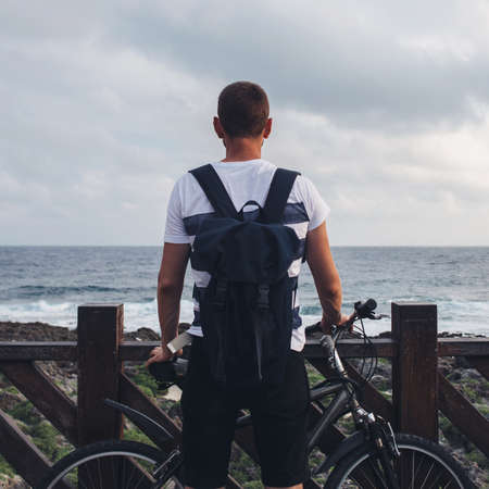 Young man with bicycle stands on the seashore and looks ahead at the sea