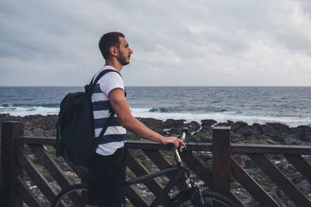 Young man with bicycle standing by the shore looking at the sea and the sky.