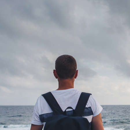 Young man standing by the shore looking at the sea and the sky.