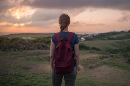 Young woman stands on a hill and looks at the opening expanse